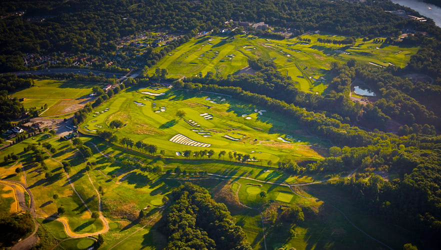 Aerial photograph overlooking a golf course during a sunset.