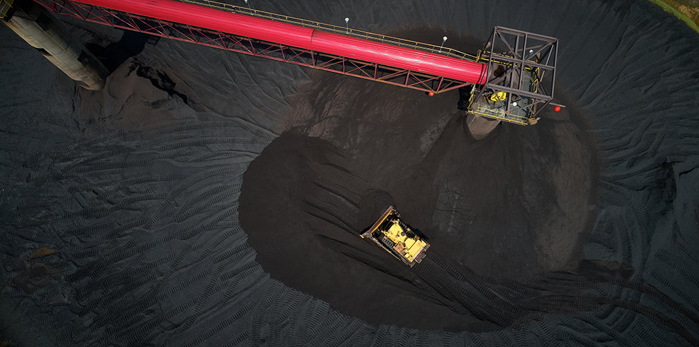 Aerial photograph looking straight down on a pile of coal while a bulldozer moves the coal around.