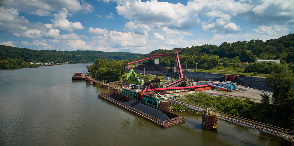 Aerial photograph of coal being loaded onto a barge.