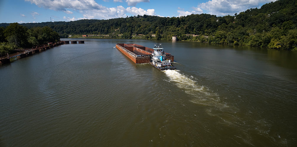 Aerial photograph of a barge going upriver.